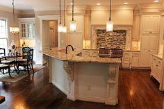 White kitchen, light granite, wood floors, stainless steel appliances.