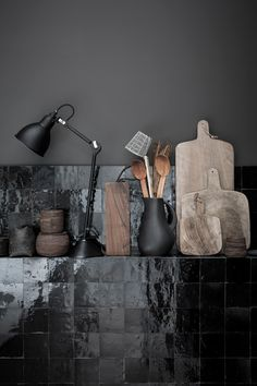 Texture is the key to creating depth in a space with a limited colour palette-I love the use of glossy tiles against the matt black lamp, vase and wooden chopping boards.