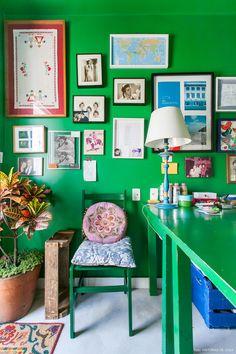 Paredes e móveis pintados de verde e parede galeria no home office desse apê.