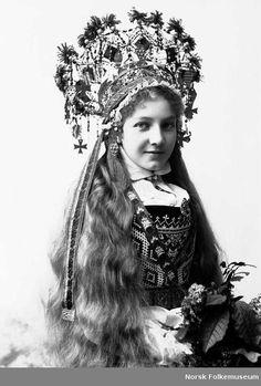 Digitalt Museum - Studiofotografi av kvinne med brudedrakt og brudekrone. Sittende med blomster i fanget. Utslått hår. Hofteutsnitt. Vendt mot høyre. Ser på betrakteren.