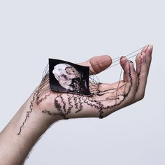 Combining visual & performance art David Cata sews family portraits into palm of his hand symbolizing people who have 'left their mark' on artist's life, just as portraits leave their mark on his skin.