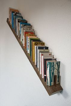 16 unique ways to store books under your stairs, including this bookshelf railing. #pimplediy