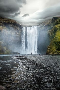 Man standing at the base of a waterfall #nature #waterfall #awesome