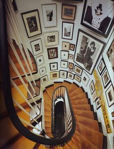 Matted and framed pictures on a spiral staircase.     A dramatic look. Definitively better than just painting the wall wouldn't you say? This is the very reason we offer so many different types of wood frames!    www.frameplace.com