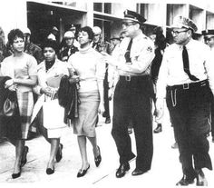 (Loro sono Janice Jackson, Evelyn Pierce ed Ethel Sawyer, appartenenti ai Tougaloo Nine. Il 27 marzo del 1961, entrarono, insieme ad altri 6 studenti e sdentesse del Tougaloo College, nella biblioteca comunale di Jackson, riservata all'epoca alla sola popolazione bianca. La polizia irruppe e i nove vennero arrestati. Le loro azioni ispirarono il movimento dei diritti civili nel Mississippi. nella foto il momento dell'arresto. è splendida l'espressione fiera di queste tre giovani donne e lo…