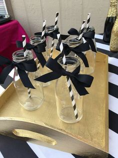 These glass bottles decorated with black ribbon and matching straws at this Kate Spade Birthday Party are awesome! See more party ideas and share yours at CatchMyParty.com