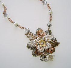 """""""Pretty Posies"""" .... a lovely necklace of red and gold brass, with a handmade vintage acrylic pearl flower centerpiece.  Some of the leaves are handpainted, and the glass faceted and pearl bead neck chain complete this day or night, winter or spring look.  More information and other goodies at www.facebook.com/NovegattiDesigns"""