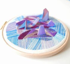Artist Justyna Wołodkiewicz mixes embroidery with abstract clay forms in order to produce three-dimensional works that spring from traditional hoops. The pieces weave together bold threads with equally bright polymer clay shapes, creating multi-textured surfaces from the diverse materials.