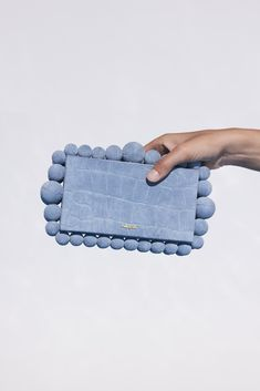 The Eos Clutch is gorgeously embellished with oversized bead detail that lines the edge of the bag and crafted from a blue-hued crocodile embossed suede leather. This statement-making bag gives off an air of 60's glamour, but easily fits a smartphone. A redefined classic, you'll endlessly turn to the Eos to accent any