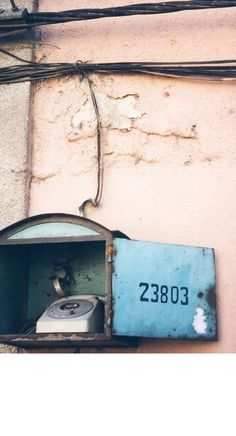 old phone booth on weathered wall in tea rose somewhere in Portugal -