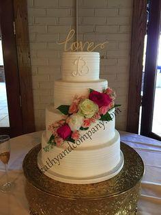Horizontal lined buttercream wedding cake with cascading fresh flowers.