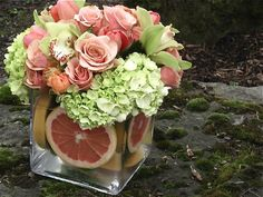 roses, hydrangeas and orchids with sliced grapefruit at the bottom of the vase - the colors are so pretty!