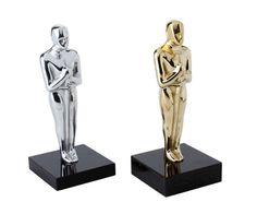 Peça: tridimensional com relevos, 21cm de altura. Materiais disponíveis: alumínio (prata) ou bronze (dourado ou patinado). Base: madeira natural ipê ou madeira revestida de fórmica preta, 10x10x2cm. Placa cortesia: aço inox (prata) ou latão (dourada), 6x2cm.