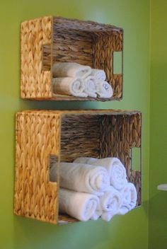 Baskets hanging on the wall with rolled up towels in them.