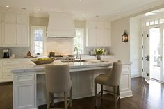 Kitchen Stools. White kitchen island with sleek marble counterop and Restoration Hardware 1940s French Upholstered Barrelback Counter Stools. #KitchenStools Anne Decker Architects.