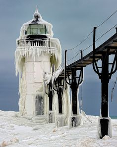 """""""Frozen Light"""" St. Joseph Northpier Lighthouse, St. Joseph, Michigan by John McCormick on Flickr. """" I had to crawl on my stomach to get around the edge of the inner Light , for a shot the ice encased outer. There was a rope tied to the structure which I tied around my waste, and untied once I reached the other side. It's about a four foot wide sloped section, 25 feet or so that you have to get across,it is extremely slippery."""""""
