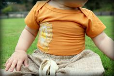 Lion wraps around baby's middle and the linen pants are so cute!  www.mybabypeanut.com