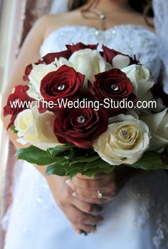 Bride's bouquet. Red & Ivory Roses with large rhinestones inside some of the flowers. The added sparkle in the floral arrangement made the bride shine! www.The-Wedding-Studio.com