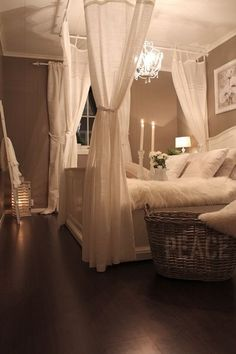 A Romantic master bedroom... love the idea of hanging the curtain rods from the ceiling... makes the bed such a cozy getaway for two :) love the chandelier. Love the paint!