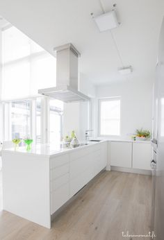Valkoinen keittiö, jossa myös liesituuletin on valkoinen ((love these floors))