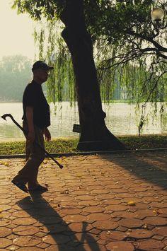 An Old man walking by the Hoan Kiem lakeside