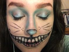 Cheshire Cat makeup. Notes: brows have to be blue. The white eyeshadow looks patchy, silver shadow too transparent- blend better (need better brushes), better liner for mouth (I think that's sorted). Also need to try using white face paint for teeth rather than eyeshadow, as it doesn't stick to lips and isn't opaque enough. Also need to practice shading the teeth. Need to adjust positioning of mouth so blue contour can be seen. Need to perfect stripe technique.