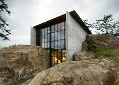 A house between rocks on the San Juan Islands in Washington state, by Seattle firm Olson Kundig Architects.