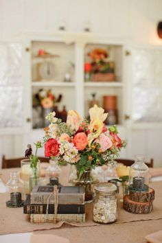 center piece with flowers, buttons, and books