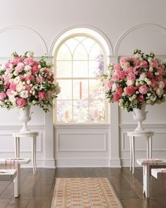 Wedding Ceremony Arrangements: The altar is flanked by a pair of glazed ceramic urns that hold classic, painterly arrangements of peonies in bright pink, light pink, and blush. Mixed in are snowball viburnum and mock orange. These majestic urns can be transported to the reception and used again there.