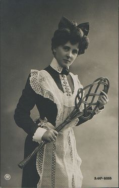 A maid in uniform, circa 1900 with a carpet beater.