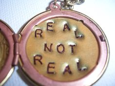 The  Hunger Games real not real hand stamped Peeta's  locket with mockingjay. $24.99, via Etsy.