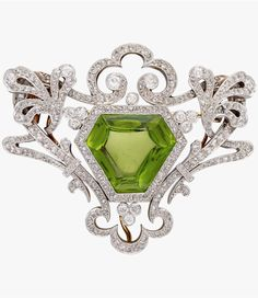 A Belle Époque peridot, diamond and platinum-topped eighteen karat gold pendant brooch, centering a modified shield-shaped peridot in a detailed rose, single and old mine-cut diamond surround. Gross weight: 17.6 dwt.; Length: 1.5 in.
