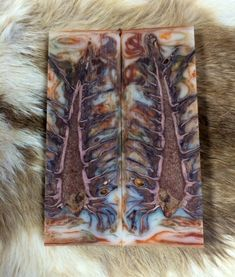 Stabilized Pinecone Knife Handle Scales within an orange/white Epoxy Resin