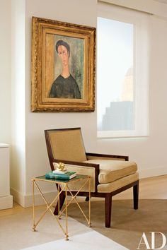 A Modigliani portrait hangs above an armchair, from Holly Hunt, and a side table, from Maison Gerard | archdigest.com
