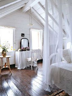 All-white bedroom, converted attic space, with original dark hardwood floor. Gorgeous!