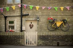 A yellow, flower-clad bike adorns a stone cottage in Holmfirth
