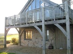 Glazed gable on first floor with oak balcony. By Roderick James Architects.
