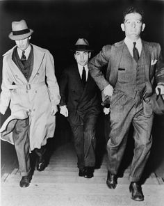 Lucky Luciano (1896-1962), being escorted into court by two detectives in 1936. Luciano was sentenced to 30-to-50-year prison term but continued to manage organize crime from prison.