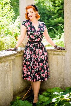 """This elegant 50s Layla Cross Over Floral Swing Dressis a true vintage beauty, perfect for any occasion!  Just like the Eric Clapton song; """"Layla, you've got me on my knees"""", wow such a beauty! The fitted bodice features a stunning V-neckline with a beautiful wrap over, two playful fixed tie straps at the side which can be worn loose or tiedand flattering pleats at the side. Made from a smooth and supple, light shiny, stretchy, black fabric with a romantic, watercolour flower print for a…"""