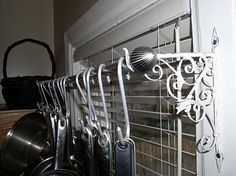 DIY Over-the-sink pot rack: Decorative wall brackets, a curtain rod, and S hooks.  Simple, cute, and CHEAP!
