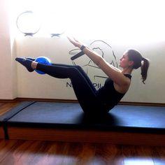 Teaser Sentada, coloque a bola entre os tornozelos e flexione os joelhos. Com as mãos atrás dos joelhos, incline o tronco para trás. Alinhe os pés com os joelhos, paralelos ao solo. Depois de estabelecer equilibrio é que chega o desafio de elevar os braços ao lado do corpo, numa diagonal à frente. Mantenha na posição 10 segundos.