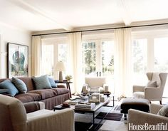 Ample and comfortable seating in earth-tone linens with cashmere pillows and throws creates a serene setting, while sheer curtains keep it light and easy. Design: Robert Stilin.