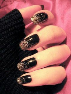 A black nail polish with a gold shine at the end.