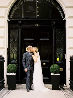 Forget the couple.  Love the door and topiaries!