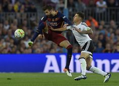 Barcelona's defender Gerard Pique (L) vies with Valencia's forward Santi Mina during the Spanish league football match FC Barcelona vs Valencia CF at the Camp Nou stadium in Barcelona on April 17, 2016.