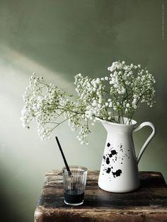 De fina emaljkannorna SOCKERÄRT fångar den romantiska sommarkänslan med bara några enkla och vackra ängsblommor. Här har vi DIY stänkdekorerat vaserna för att smälta in i grönskan.