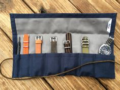 Simple, stylish, and handmade, our watch rolls are designed for watch collectors and enthusiasts. Handcrafted for storage and travel, this compact and convenient roll can also be used for camping, craft storage, or knife collectors. It features 5 watch pockets, 1 strap pocket, and 1 spring bar tool pocket, and fits up to a 43mm watch case*. Made with a durable duck fabric shell, a 100% cotton fabric lining,and a 23 leather cord. 14 x 9 open/14x 6 closed. At hub city vintage, we are pass...