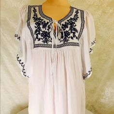 White peasant top with blue embroidery. Adorable, fantastic blue embroidery. The bust is about 42 inches around, and the length is about 26 inches. The material is a beautiful lightweight 100%. Rayon. Tops Blouses