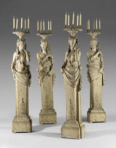 Suite de quatre termes porte-torchère en bois sculpté peint à l'imitation du marbre blanc veiné représentant deux couples sculptés à l'identique, les femmes portant une tresse et les hommes, un ruban barrant leur front.  Les têtes sont surmontées d'une tablette ronde sculptée d'une frise de laurier, reposant sur des chutes de guirlandes de fleurs.  Les bases en gaine sont ornées de draperie frangée et de feuilles d'acanthe.  Epoque Louis XV.