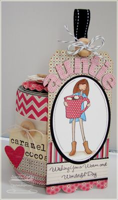 decorating a tin can (with a treat inside, original packaging) with patterned paper, a tag, and rosette to top it off; so cute